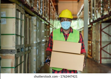 porttrait of african american factory warehosue woker with safety vest and helmet wearing face mask to protect coronavirus covid-19 holding boxes at factory warehouse