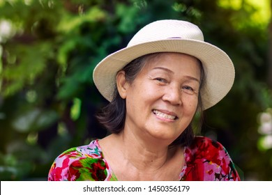 Porttrait image of 60s or 70s Asian elderly woman in colorful outfit with hat.Beautiful old lady smiling in the park.Concept of Happy healthy retired senior people.