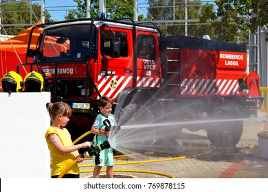 Portugal, Algarve, Lagoa, Circa 04.06.2017 Children learning how to be firefighters using fire hoses  at a local international fair in the Algarve, Portugal. Potugal has many forest fires every year.