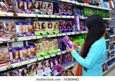 Portugal, Algarve, Monchique. Circa 18.12.2013. Young woman choosing hair dyes, colouring in a supermarket. Image taken on the 18th of December 2013 in Intermarche supermarket.