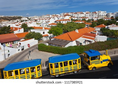Portugal.  Algarve. Tourists travel through the old town Albufeira on the on a bright train-bus