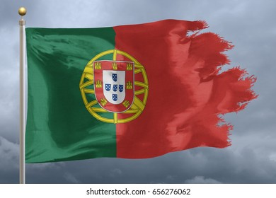 Portugal Flag with torn edges in front of a stormy sky