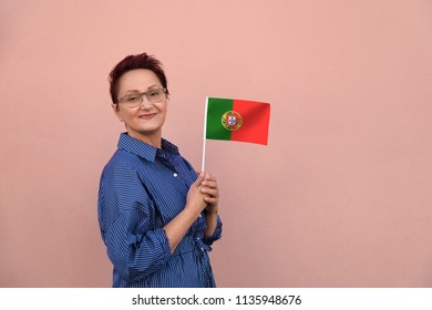 Portugal flag. Woman holding Portuguese flag. Nice portrait of middle aged lady 40 50 years old with a national flag of Portugal over pink wall background.