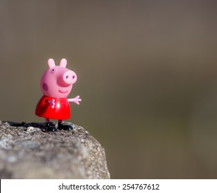 Portugal - January 10, 2015 : Figure of Pepa Pig from Astley Baker Davies / Entertainment One UK animations, standing on a rock in my farm, Povoa de Lanhoso
