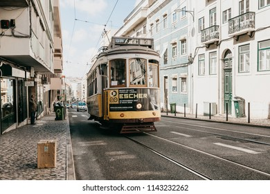 Portugal, Lisbon, June 01, 2018: A traditional yellow old-fashioned or retro style tram ride down the city street.