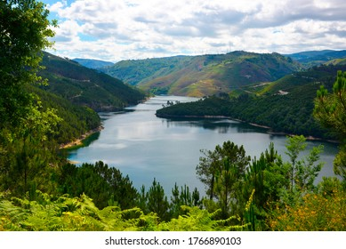 Portugal Northern landscape. Geres National Park, green mountain slopes, Cavado river and cloudy blue spring sky, Braga District.