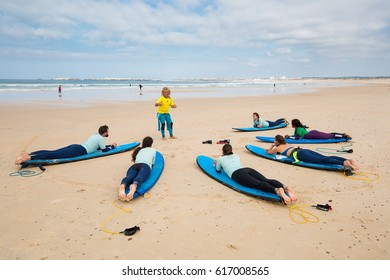 Portugal, Peniche - October 10, 2016: Surfing coach instructs novice surfers on the beach near the ocean. Students are on their surfboards around the coach.