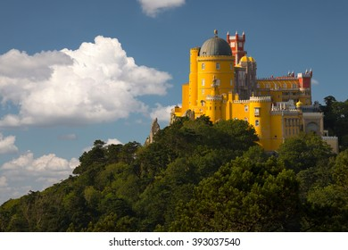 Portugal. Sintra. The Pena Palace on a cliff surrounded by forest and clouds