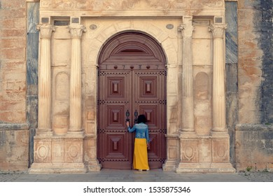 Portugal tourist attraction concept. A girl is standing at the doors of Santa Maria church in the beautiful, mediaeval town of ?bidos, one of the most picturesque and well preserved in Portugal.