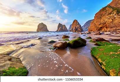 Portugal Ursa Beach at atlantic coast of Atlantic Ocean with rocks and sunset sun waves and foam at sand of coastline picturesque landscape panorama. Stones with green moss in front.