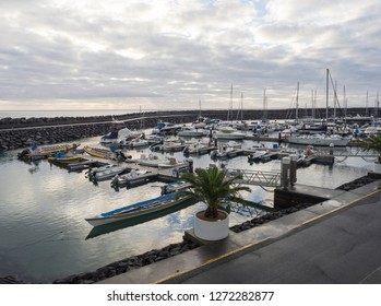 Portugal, VILA FRANCA DO CAMPO, Sao Miguel, Azores, December 20, 2018: Colorful fishermen boats and Yachts in marina of Vila Franca do Campo town, early morning cloudy sky