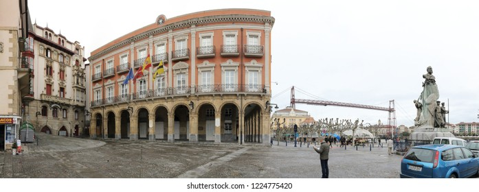 Portugalete, Spain - December 09, 2017: The Plaza del Solar square, with its 1800 neoclassical city hall and the aerial Vizcaya bridge, in Portugalete town, Basque Country, Spain