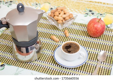 Portuguese cup of expresso coffee with goober peanuts and fruit on a bamboo rolling mat.