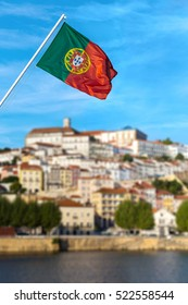 Portuguese flag with blurred old university city of Coimbra in the back, the medieval capital of Portugal, view from the river. Popular touristic destination and attraction.