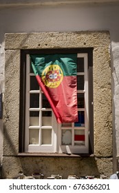 Portuguese flag in an old window in medieval town of Obidos in Portugal.