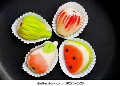 Portuguese marzipan made in various fruit patterns. Delicious fine sweets from the Algarve. Four colorful traditional Portuguese almond marzipan cakes. Top view isolated on a black background.