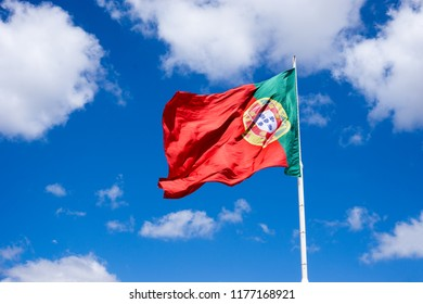 Portuguese national flag waving in the wind against blue sunny sky with white clouds, Portual