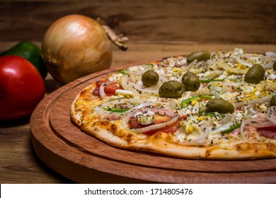 Portuguese Pizza, onion, peppers, pepperoni, egg, olive on wooden background