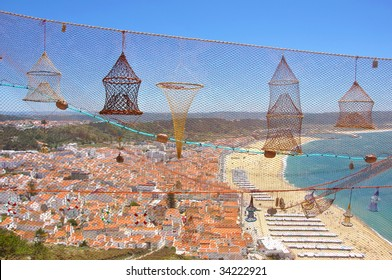 Portuguese seaside town viewed through a display of small souvenir fishnets on a sunny day, focus set on the net