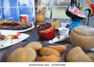 Portuguese specialty assortment. Stuffed tomato, beef, samosa and tapas, struder with spice sauce. Served on wooden table with portugese decoration.