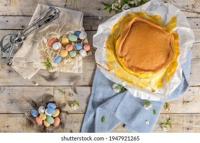 Gâteau d'éponge portugais enveloppé dans le papier typique utilisé sur la cuisson, sur fond bois avec décoration d'oeufs de Pâques peints.