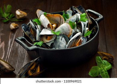 Portuguese-Style Mussels in Garlic Cream Sauce with parsley in a bowl. Delicious European meal on a table.