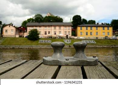 PORVOO, FINLAND  - AUGUST 3, 2016: View of the old Finnish town of Porvoo across the river, wooden jetty and berth bollard