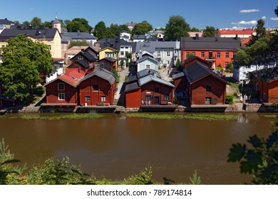 PORVOO, FINLAND - JULY 16, 2017: People resting on the river Porvoonjoki in the center of town. The red-colored wooden storage buildings on the riverside are a proposed UNESCO world heritage site