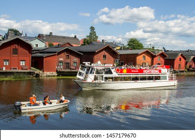 Porvoo, Finland - July 20. 2019 -  Porvoo Line's sightseeing boat Queen passing small motor boat on the Porvoo River - Historical red wooden river bank houses on the background