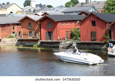Porvoo, Finland - July 28, 2019: Motorboat in river Porvoo (Porvoonjoki in Finnish) and old wooden red houses on the riverside.