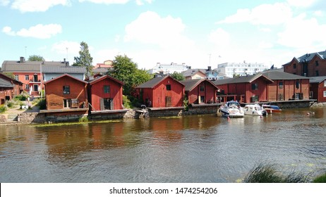 Porvoo, Finland - July 28, 2019: Boats on river Porvoo and old historic red wooden houses.