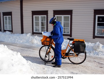 PORVOO, FINLAND - MARCH 9, 2012. The woman postman delivering post to local people on the service bicycle March 9, 2012 in Porvoo, Finland