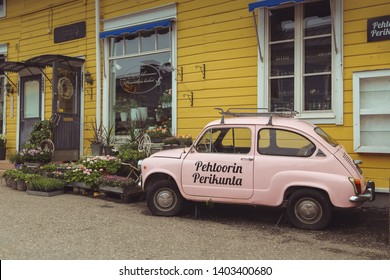 Porvoo, Finland - may 2019: old retro pink Fiat 500 on yellow wall background. Produced by the Italian manufacturer Fiat from 1957 to 1975.