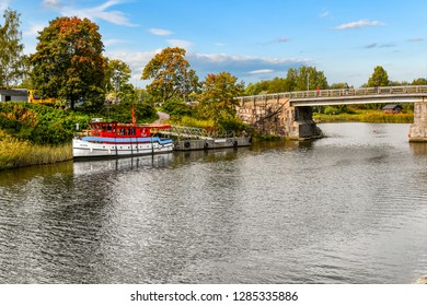 Porvoo, Finland - September 10 2018: A boat docks along the banks of the Porvoonjoki river as visitors cross the bridge connecting to the medieval village of Porvoo, Finland.