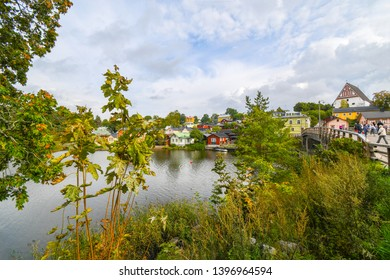 Porvoo, Finland - September 10 2018: The 15th century Porvoo Cathedral rises above the medieval town of Porvoo, Finland, as tourists make their way across a bridge over Porvoonjoki River.