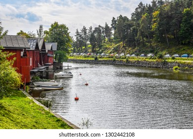 Porvoo, Finland - September 11 2018: Waterfront homes with boat docks line the Porvoonjoki River on a peaceful summer day in the medieval village of Porvoo, Finland.