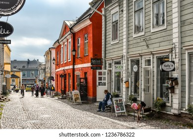 Porvoo, Finland - September 14 2018: Tourists and local Finns walk past shops along the cobbled streets of the medieval old town section of Porvoo, Finland.