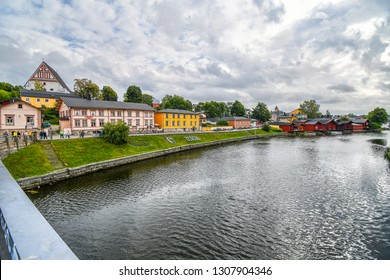 Porvoo, Finland - September 14 2018: Tourists walk along the Porvoonjoki river adjacent to the medieval village and waterfront homes of Porvoo, Finland in early autumn