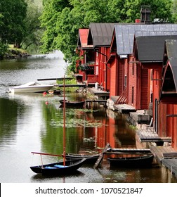 Porvoo river and it's scenic row of old rust-red warehouses facing the calm water with reflections