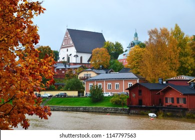 Porvoo river and it's scenic row of old rust-red warehouses facing the calm water with reflections in fall with colorful autumn leaves