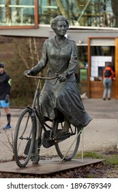 Posbank, The Netherlands - December 28, 2020: Closeup of statue sculpture of queen Beatrix riding a bike in front of the central pavilion in the Dutch national park inside the Veluwe region