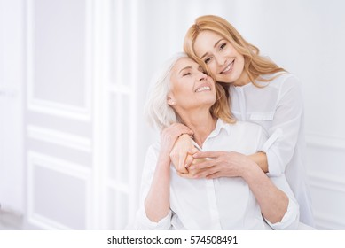 Posditive woman and her adult daughter resting at home