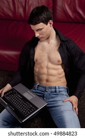Pose of handsome sexy young man with laptop. Wearing black shirt, jeans, showing muscle body.