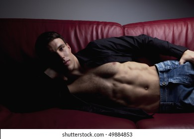 Pose of handsome sexy young man. Wearing black shirt, jeans, showing muscle body.