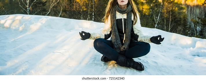 pose lotus. no face. brunette woman sitting in winter park under fur tree. young woman doing yoga lotus position in winter snow covered park. peak of mountain. knitted gloves on hands
