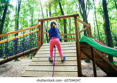 Pose of a young child climbing on a rope in park