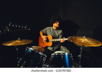 Pose of a young guitarist man wearing a black wig and playing the guitar while sitting near the drums in a musical studio.