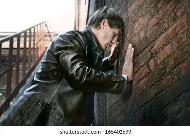 Pose of young sad guy near old brick wall