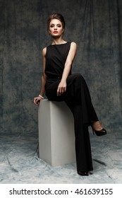 Posh, confident and stylish business lady with red lips wearing black smart jumpsuit is posing on the cube in the studio