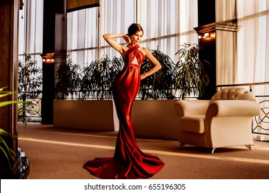 Posh glamorous model in evening long red dress posing in hotel. Fashion photo